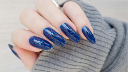 Female hand with long nails and blue manicure with bottles of nail polish Imagens