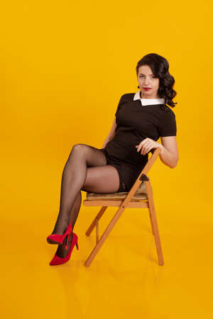 Young brunette girl in a short black dress posing on a wooden chair on a yellow background 免版税图像