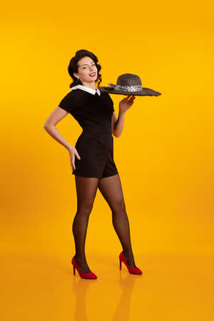 Young brunette girl in a short black dress holds a black hat with large brim and poses on a yellow background Foto de archivo