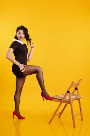 Young brunette girl in a short black dress posing on a wooden chair on a yellow background Foto de archivo