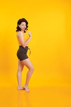 Young brunette woman with pin-up hairstyle in shorts holds lollipop in her hands and poses on a yellow background