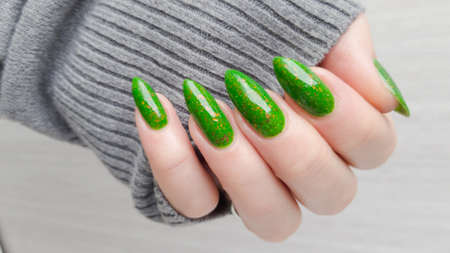 Woman's hand with long nails and green manicure with bottles of nail polish