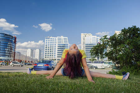 Brunette girl dancing, jumping, doing acrobatics and posing, in a city park near the lake on a sunny day