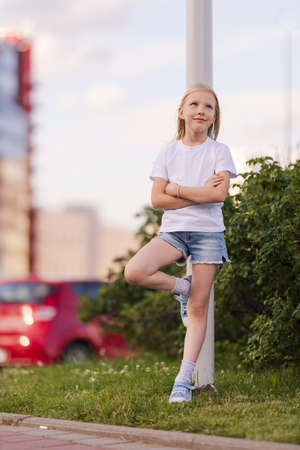 Blonde girl dancing, jumping, doing acrobatics and posing, in the city against the backdrop of buildings on a sunny day
