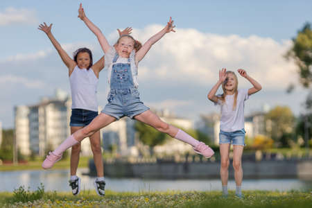 Children girls friends run, jump and pose near a lake in a city park on a sunny day