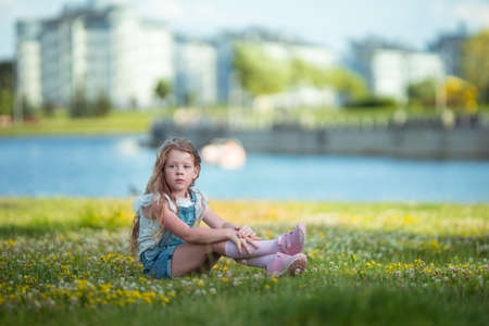 Blonde girl dancing, jumping, doing acrobatics and posing, in a city park on green grass near a lake on a sunny day Stockfoto