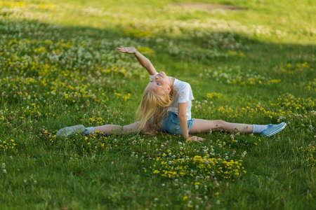 Blonde girl dancing, jumping, doing acrobatics and posing, in a city park on green grass near a lake on a sunny day
