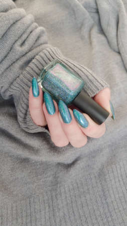 Woman's hand with long nails and turquoise blue manicure with bottles of nail polish Фото со стока