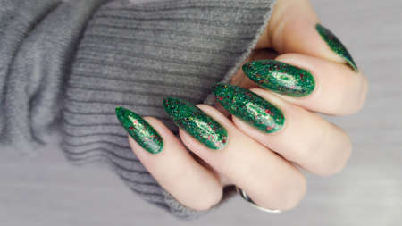 Woman's hands with long nails and a green manicure holds a bottle of nail polish
