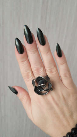 Woman's hands with long nails and black manicure with bottles of nail polish Фото со стока