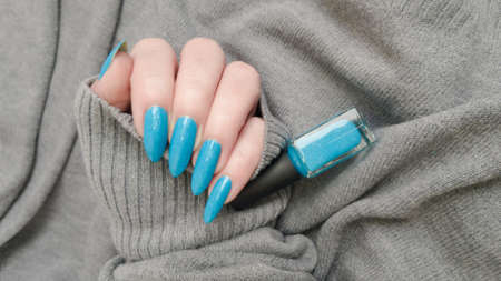 Woman's hand with long nails and turquoise blue manicure with bottles of nail polish