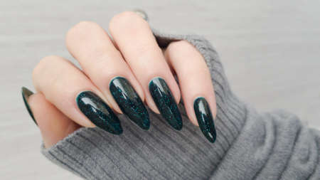 Female hand with long nails and dark color manicure with bottles of nail polish
