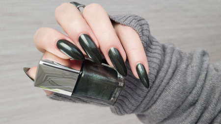 Woman's hands with long nails and black manicure with bottles of nail polish