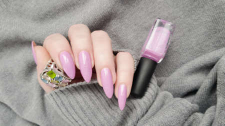 Woman hand with long nails manicure and pink fuchsia bottle with nail polish
