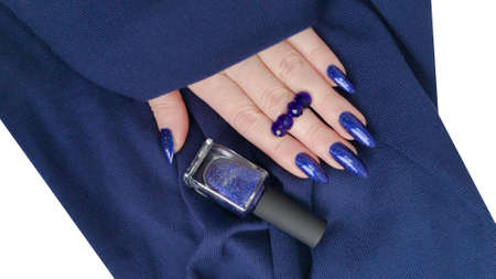 Woman's beautiful hand with long nails and blue manicure with bottles of nail polish