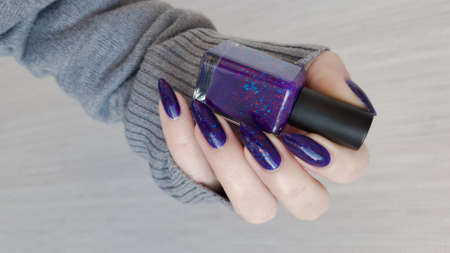 Woman's hands with long nails and a bottle of purple lilac color nail polish