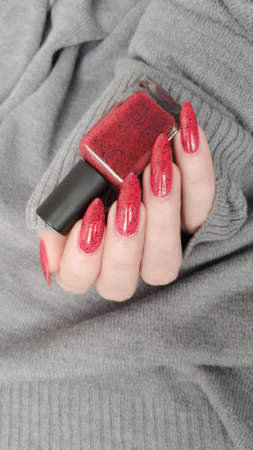 Female hand with long nails and a bottle of bright red nail polish