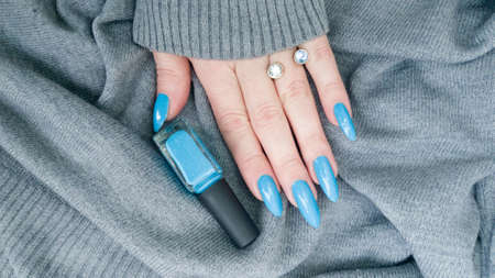 Woman's beautiful hand with long nails and blue manicure with bottles of nail polish Фото со стока