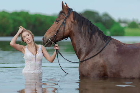 Young blonde girl in a white long dress swims in the lake with a brown horse on a sunny day Standard-Bild - 153478791