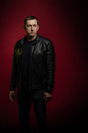 Brutal man in a black leather jacket poses against a dark red background