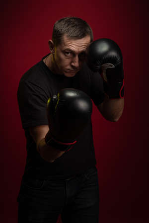 Male athlete boxer with gloves in his hands posing against a dark red background