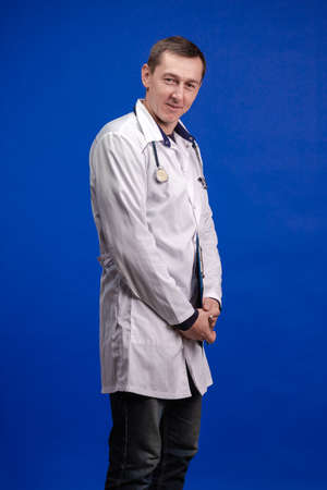 emotional adult male doctor in a white coat posing on a blue background