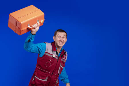 Ambulance doctor man in a medical uniform and with a box in his hands posing on a blue background