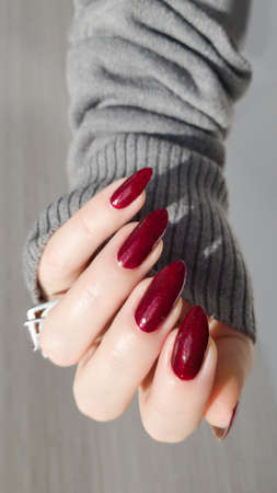 Female hand with long nails and a bottle of dark red nail polish Imagens