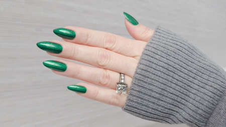 Female hand with long nails and a green manicure holds a bottle of nail polish Zdjęcie Seryjne