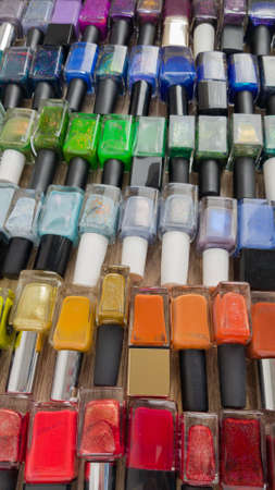 Background for design. A multi-colored bottles with nail polishes laid out on the wooden table Reklamní fotografie