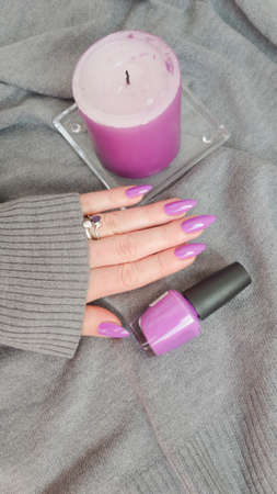 Woman hand with long nails manicure and pink bottle with nail polish