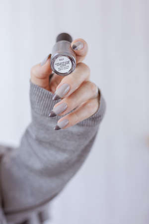 Female hand with long nails holds a bottle of gray-brown thermo nail polish