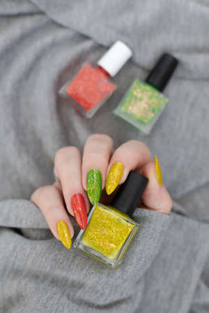Female hand with long nails and multi-colored manicure, bottles of nail polishes