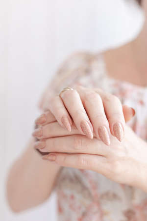 Female hand with long nails and a bottle of beige nail polish