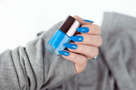 Female hand with long nails and light blue manicure with bottles of nail polish