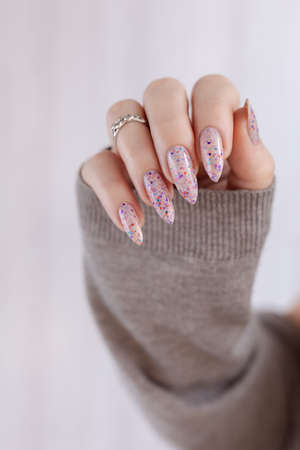 Female hand with long nails and light pink manicure holding a bottle of nail polish.