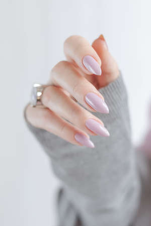 Female hand with long nails and a bottle of beige pink nail polish