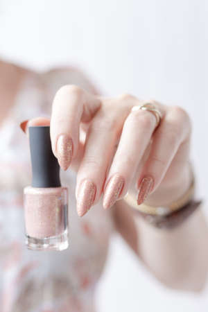 Female hand with long nails and a bottle of beige pink nude nail polish