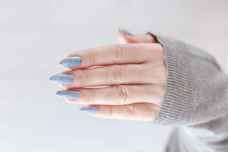 Female hand with long nails and light blue manicure with bottles of nail polish Banque d'images