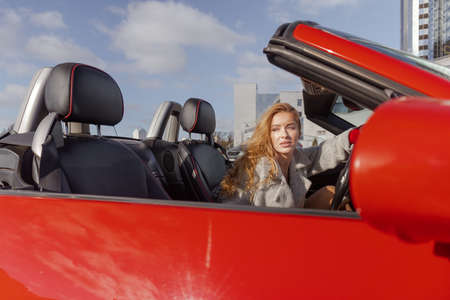 Beautiful young blonde woman in a red dress posing in a red car in the city on a sunny day