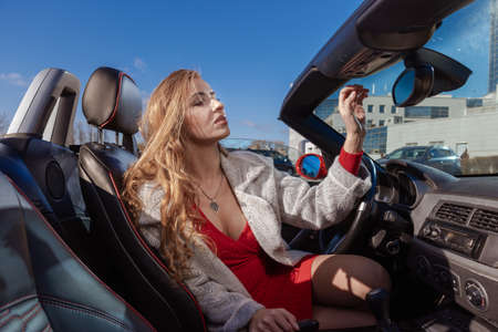 Young blond woman posing with red car