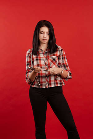Girl master plumber in a plaid shirt holds a hose and an adjustable wrench in her hands and poses on a red background Zdjęcie Seryjne