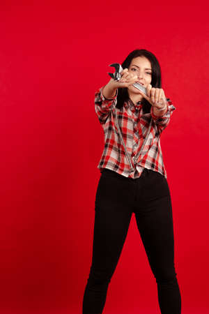 Girl master plumber in a plaid shirt holds a hose and an adjustable wrench in her hands and poses on a red background