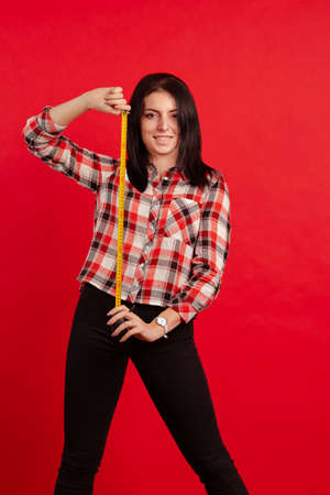Girl master designer in a plaid shirt with a measuring tape in hands posing on a red background