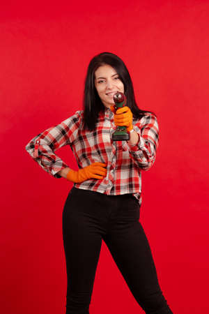 Builder girl in a plaid shirt and orange gloves holds an electric drill and poses on a red background