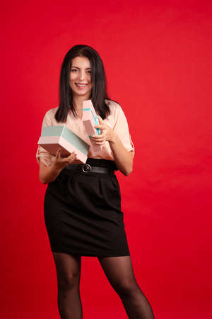 Young brunette girl in a blouse and a black skirt with a gift in a pink box in hands posing on a red background