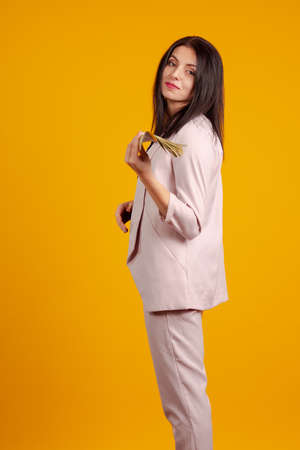 Young brunette girl in a pantsuit with a bundle of banknotes money in hands on a yellow background