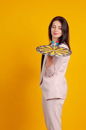 Young brunette girl in a trouser suit with a dartboard in hand on a yellow background