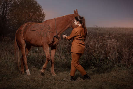 Young brunette woman in a red brown trouser suit posing with a brown horse. Sunset sky and autumn nature. The inscription on the horse: have fun.