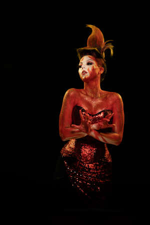 Young woman dancing in a fantasy image Flames and Fire in red body art emotionally posing on a black background.